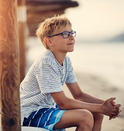 Cute boy enjoying sitting on a seabed and looking at the sea on sunset. Nikon D850