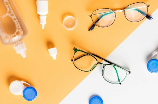 Optical glasses, contact lenses and eye drops on a yellow and white background, top view, flat lay.